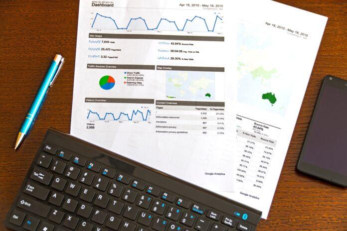 mesa con hojas llenas de gráficos, teclado y bolígrafo