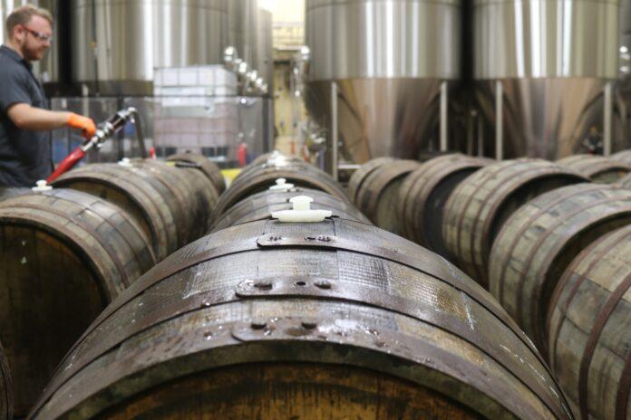 barriles de madera con cerveza en fábrica
