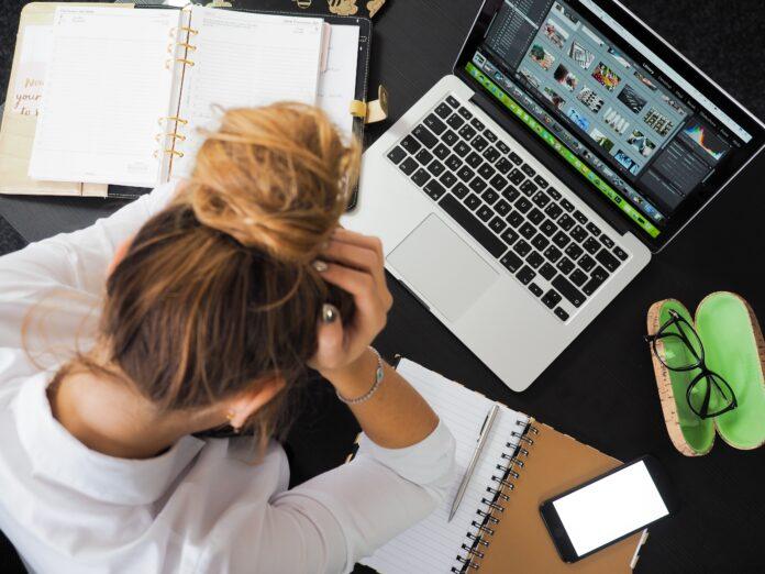 escritorio de diseñadora y persona en señal de frustración