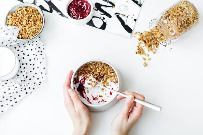 una persona mezclando yogur y cereales en un bol