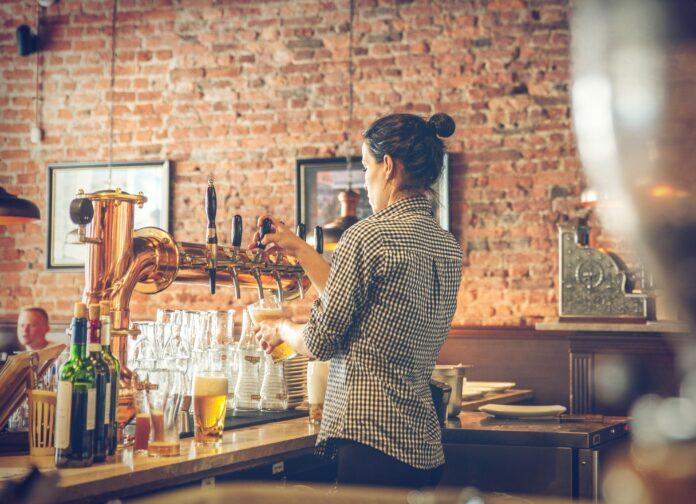 chica sirviendo cervezas en una barra vacía