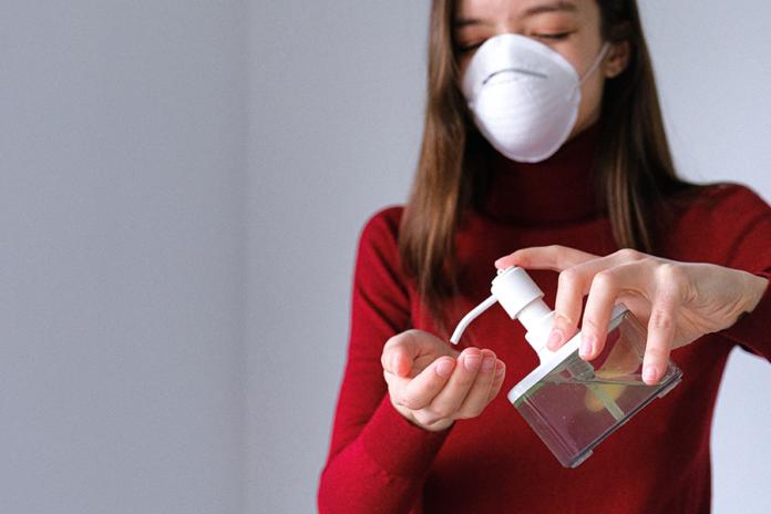 Mujer echándose gel hidroalcohólico en las manos con mascarilla