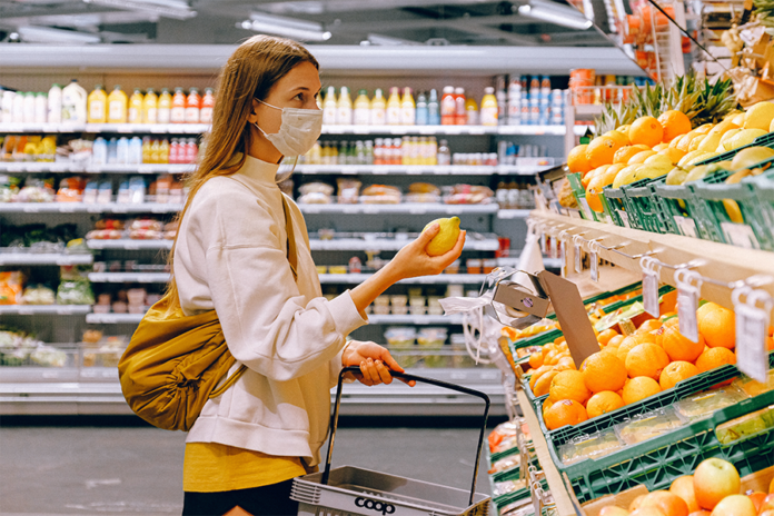 mujer con camisa blanca comprando con mascarilla en el super