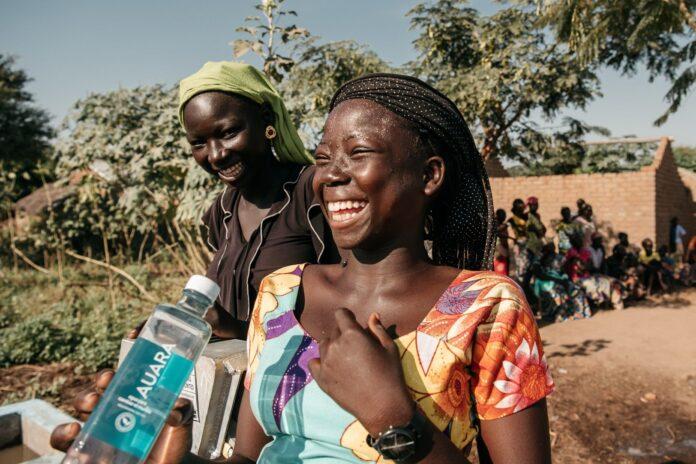 mujer africana riendo con una botella de agua en la mano