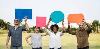 4 personas llevando carteles de colores en forma de diálogos
