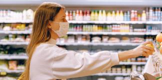chica cogiendo fruta en un supermercado