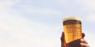 mano sujeta un vaso de cerveza al aire