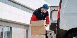 hombre cargando cajas de cartón a furgoneta