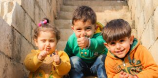 3 niños saludando a cámara