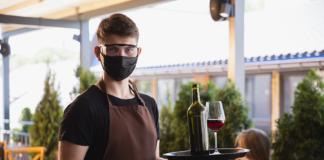 camarero con mascarilla sirviendo en bandeja