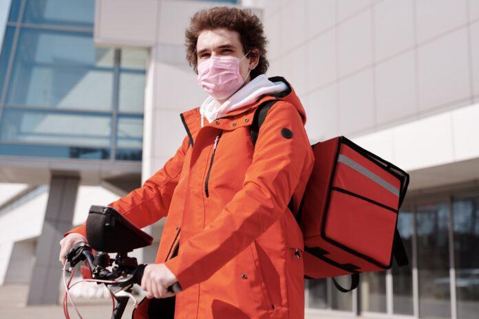 repartidor de comida a domicilio con mochila y bici