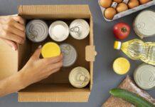 vista picada de una mano metiendo alimentos en cajas
