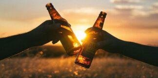 dos personas brindando con botellas de cerveza damm