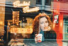 mujer tomando café en una cafetería y mirando por la ventana