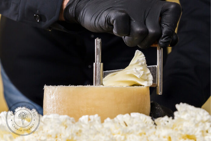 mano con guante negro elaborando una flor de queso