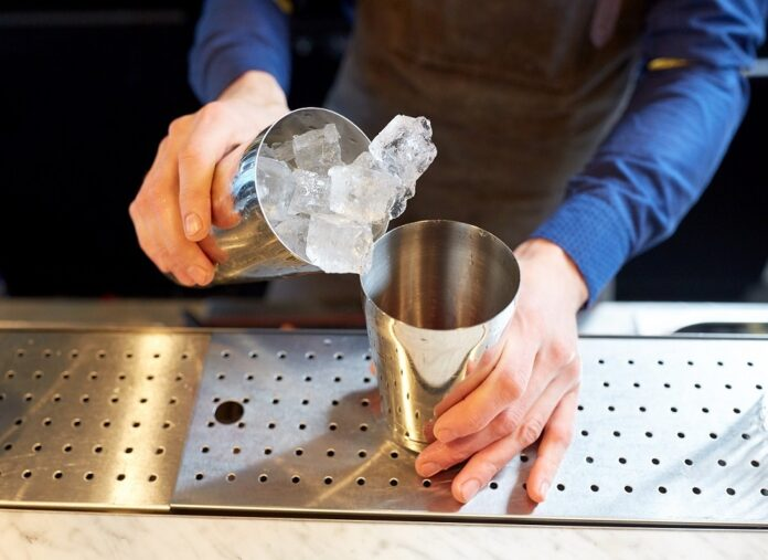 Bartender With Ice And Shaker At Cocktail Bar