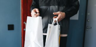 hombre entregando dos bolsas de papel blancas
