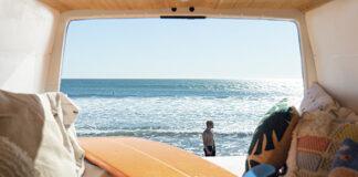 Viajes Sostenibles camper con mar al fondo y tabla de surf