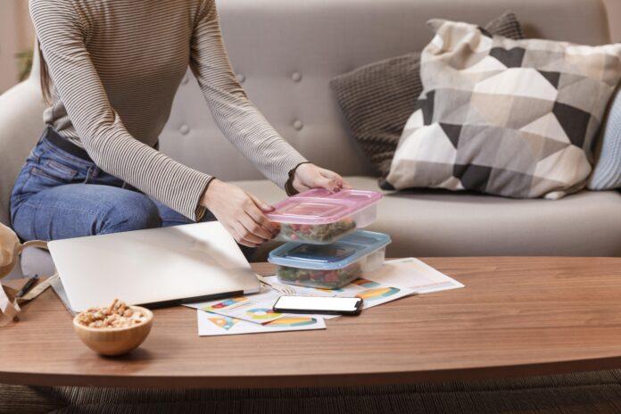 mujero cogiendo unos tappers de la mesa de su casa