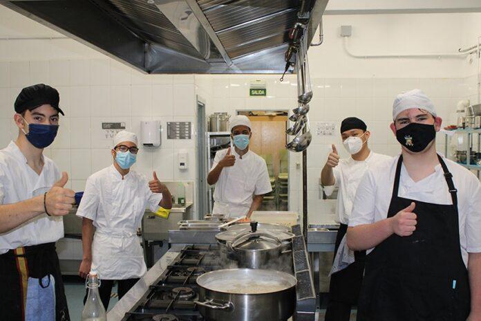 jóvenes en cocina saludando a la cámara