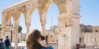 turista haciendo fotos a monumento griego-romano