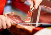 Professional Cutter Carving Slices From Whole Bone In Serrano Ham